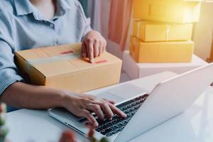 close-up beeld van de online winkel van de vrouw, de verkoper van de kleine ondernemer, het verpakkingspakket van de ondernemer, de postverzenddoos die het leveringspakket op de tafel voorbereidt, het ondernemende zelfstandige bedrijfsconcept foto