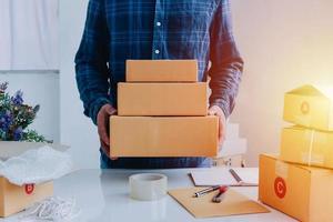 vergrote weergave van de online winkel van de man, verkoper van kleine bedrijven, ondernemer verpakking pakket post verzending doos levering pakket op tafel voorbereiden, ondernemend zelfstandig bedrijfsconcept foto