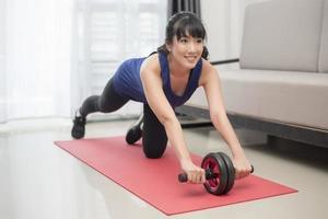 mooie sportieve vrouw doet thuis buikspieroefeningen met wiel foto