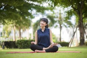 mooie yogavrouw op groen park foto