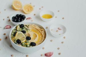 hummus van kikkererwten, met olijfolie, olijven, citroen, knoflook, sesamzaadjes, uien en komkommers. foto