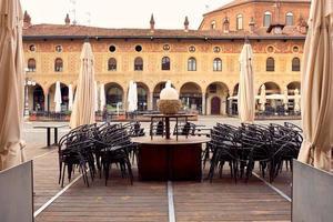 tafels en stoelen in een openluchtrestaurant in vigevano foto