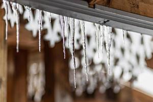 een grote transparante ijspegel hangt aan het dak van het huis. wintervorst foto