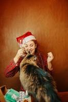 vrouw in kerstmuts houdt glas tabletten vast en speelt met kat. foto