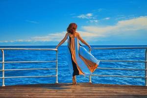 mooi meisje in vloeiende lange jurk staat op de rand van de pier. foto
