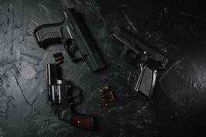drie geweren en kogels op zwarte tafel. foto
