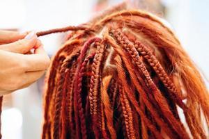 close-up van vlechtproces Afrikaanse vlechten met gekleurde kanekalon. foto
