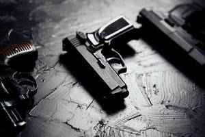drie geweren op zwarte tafel. foto