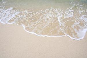 de bovenhoek van het strand heeft een zee van water dat naar de kust komt foto