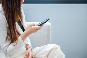 zakenvrouwen dragen witte kleren die graag mobiele telefoons spelen op een witte achtergrond foto