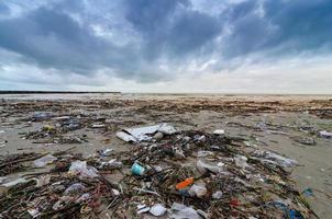 afval de strandzee plastic fles ligt op het strand en vervuilt de zee en het leven van het zeeleven gemorst afval op het strand van de grote stad. lege gebruikte vuile plastic flessen foto
