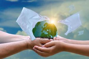 plastic tassen eten de wereld bij de hand. het concept van bedreigingen van plastic afval. foto