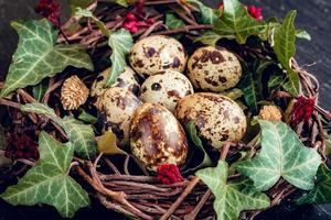 paaseieren met decoratie. kwarteleitjes in een vogelnest. foto