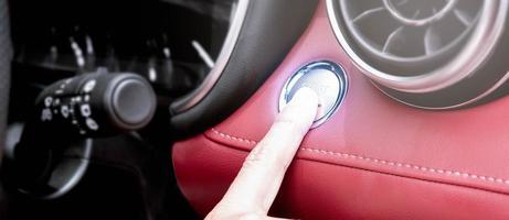 close-up van de vinger die op de knop drukt om de motor van een auto te starten. foto