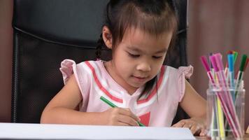 een schattig klein meisje tekent een regenboog op papier met kleurpotloden aan tafel thuis. foto