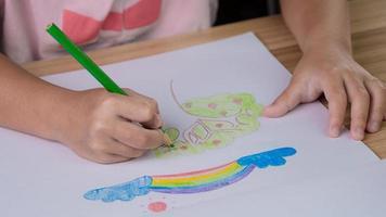 close-up hand van kind tekenen van een regenboog en boom met kleurpotloden aan de tafel thuis. foto