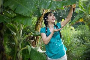 portret van een jonge Aziatische vrouw met zwart haar met een bananenblad in het regent op de groene tuin achtergrond foto