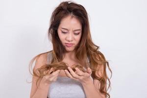 Aziatische vrouw bezorgd over haaruitval op witte achtergrond. foto