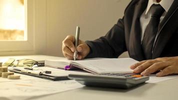 zakenlieden documenteren financiën bij het raam en warm zonlicht financieel beheer ideeën en werkpapier. foto