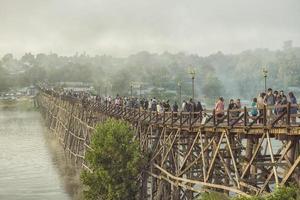 toeristen lopen op de houten brug over de rivier in kanchanaburi, thailand 2018 foto