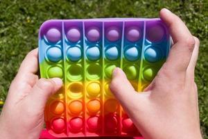kleurrijke anti-stress sensorische fidget push pop it speelgoed in kinderhanden foto