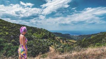 vrouw met gekke roze haarkleur. vrouw met roze haarkleur die naar de camera kijkt, aan de horizon zien we een klein stadje nea skioni vanaf een van de hoogste punten op het schiereiland kassandra, griekenland. foto