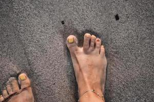 een vrouw met een gekke nagellak die een voetafdruk in het zand probeert te maken. foto