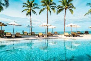 prachtig tropisch strand en zee met parasol en stoel rond zwembad in hotelresort foto