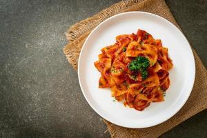 farfalle pasta in tomatensaus met peterselie - italiaans eten foto