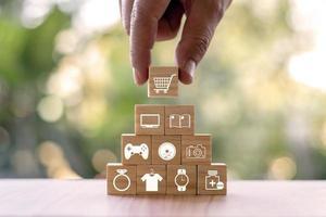 een jonge vrouw selecteert een winkelwagenpictogram en een winkelwagenpictogram op een houten blog, een online bedrijfsidee en een gids voor het maken van slimme en veilige consumptiekeuzes. foto