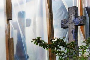 oude begraafplaats in reconstructie met blauw kruis achter een struik en bedekt met plasticfolie op houten steunen foto