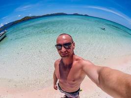blanke man maakt selfie op het strand van flores taka makassar foto