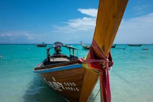 longtailboot bij het strand van de zonsopgang van Koh Lipe in Thailand foto