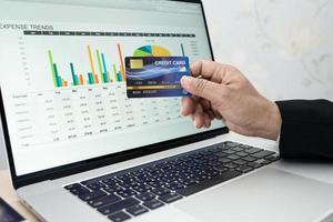 Aziatische accountant werkt, berekent en analyseert rapportprojectboekhouding met notebook en creditcard in modern kantoor-, financiële en bedrijfsconcept. foto