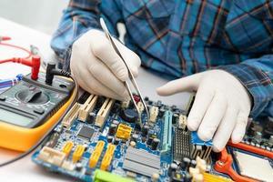 technicus die de binnenkant van de harde schijf repareert door soldeerbout. geïntegreerde schakeling. het concept van gegevens, hardware, technicus en technologie. foto