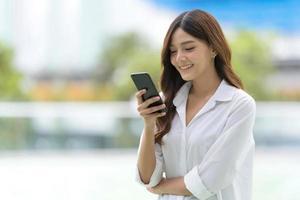 buitenshuis portret van gelukkige jonge vrouw met behulp van een telefoon foto