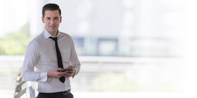 portret van lachende zakenman die op tablet gebruikt foto
