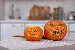 halloween pompoenen glimlach en enge ogen voor feestavond. close-up van enge halloween-pompoenen met ogen op tafel thuis. selectieve focus foto