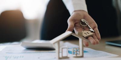 huismodel en sleutel op tafel voor financiën en bankwezen concept.home aankoop hypotheek concept. foto