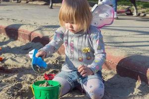 mooi klein meisje met sprookjesvleugels die het zand spelen foto