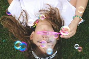 bovenaanzicht van een mooi klein meisje dat op het gras ligt en zeepbellen blaast foto