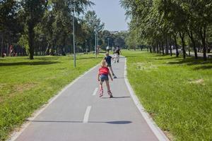 klein meisje geniet van rolschaatsen in de buitenlucht, op een warme zonnige dag foto