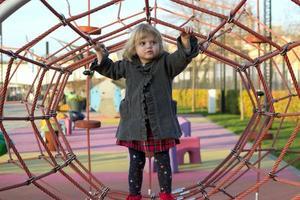 schattig klein meisje dat op de speelplaats speelt foto