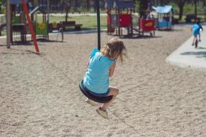klein meisje kabelbaan rijden op speelplaats foto