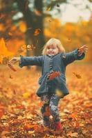 gelukkig klein meisje dat gele herfstbladeren in de lucht gooit in het park, herfstachtergrond foto