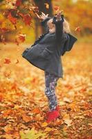 mooi klein meisje dat oranje herfstbladeren in de lucht gooit in het park, herfstachtergrond met kopieerruimte foto