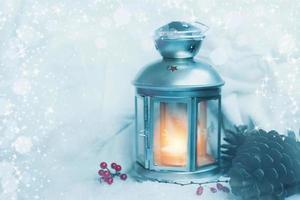 kerstlantaarn met sneeuwval Kerstmis achtergrond met dennenappels en decoratie kopie ruimte foto