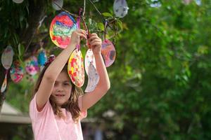 schattig klein meisje hangt aan de boom haar paaskaarten in eivorm, voor veel geluk en met goede wensen foto