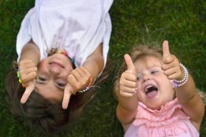 twee kleine meisjes die op het gras liggen, lachen en duimen opsteken foto