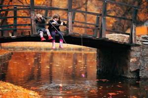 twee kleine meisjes die op een houten brug zitten en doen alsof ze vissen foto